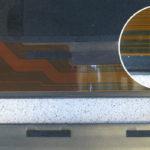 Das aufgefaltete Display-Folienkabel ist in der Mitte beschädigt (siehe vergrößerten Ausschnitt).