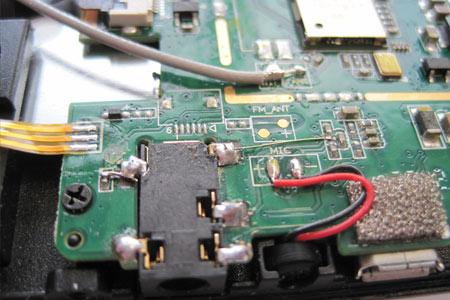 Schön zu sehen sind die Fädeldrahtverbindungen von zwei Lötpads der Kopfhörerbuchse zu den messtechnisch ermittelten potentialgleichen Anschlusspunkten auf der SMD-Platine.