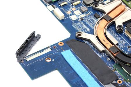 Die defekte SATA-Anschlussbuchse ist bereits entlötet und das Ersatzteil liegt bereit um mit dem Mainboard verschraubt und verlötet zu werden. Schön zu sehen auch das Schaumstoffteil zum späteren Schutz der Festplatte.