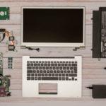 Zerlegtes Notebook. Display-Einheit, Topcase mit Tastatur, Mainboard, Festplatte, Lüfter, Netzteil.